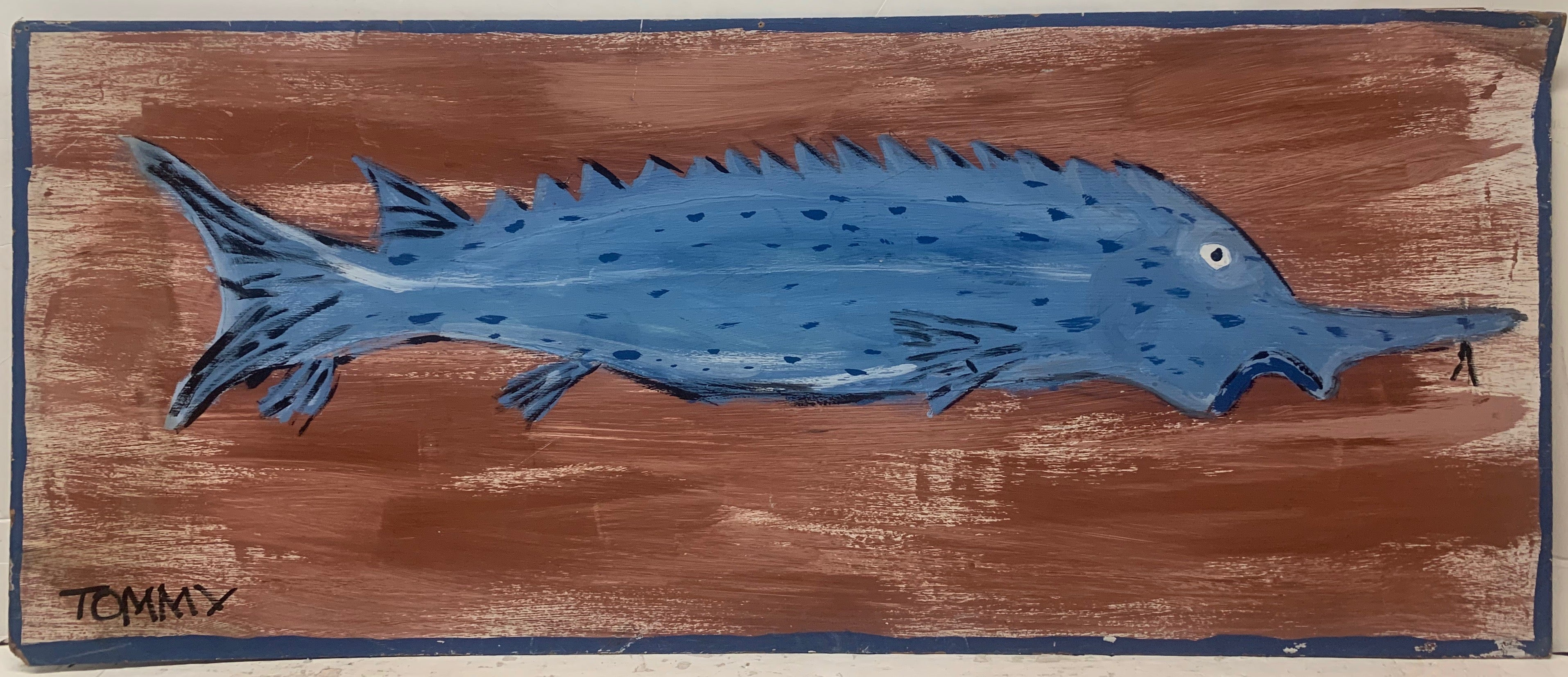 A Tommy Cheng painting of a blue fish with spikes on a brown background.