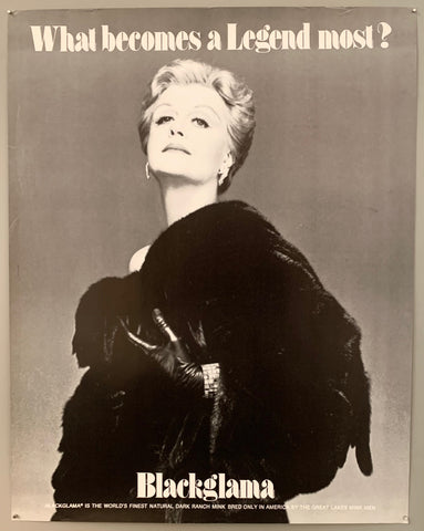 A woman with short blonde hair stares triumphantly at the camera, her coat slightly off her shoulder and with leather gloves. The text is on the top and the bottom in black.