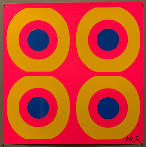 A square of four large motifs on paper. The colors are neon pink with yellow and blue targets