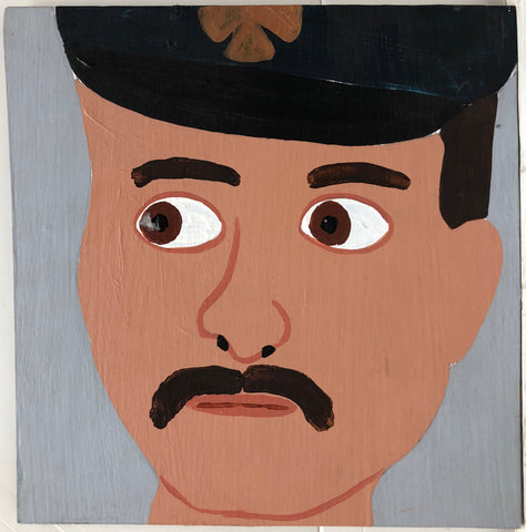Portrait of Christopher Blackwell, moustached and in a black firefighter's hat.