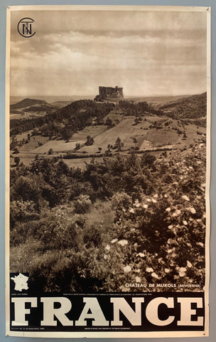 This poster is sepia toned with bold black-and-white writing at the bottom, as well as a tiny map of France. The photograph takes up the majority of the page, with a stamp of the French government at the top left. The photograph mostly contains rolling hills with farmland and trees, and the castle is in the middle, with the sky above it.