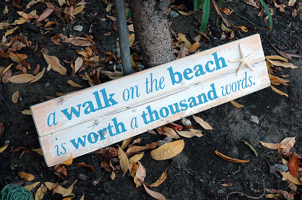 a walk on the beach is worth a thousand words sign