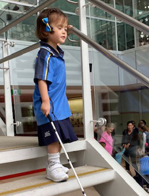 Gemme walking down steps using a white cane