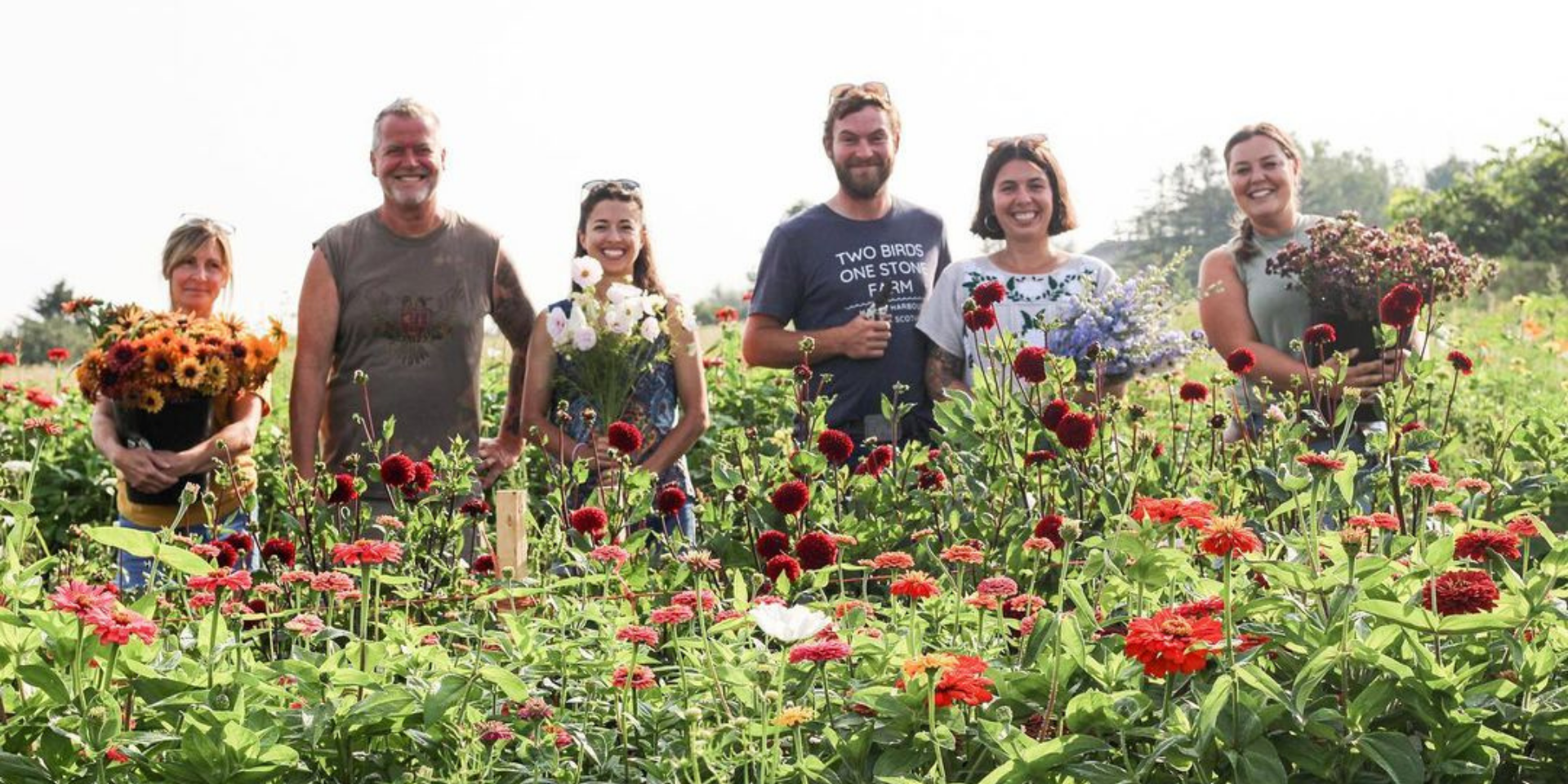 Image of team in the field holding flowers