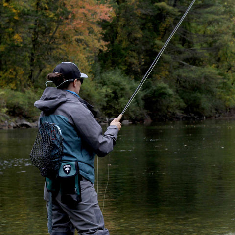 A lady fly fisher fights a trout while wearing the VEDAVOO Hip Pack and Netster