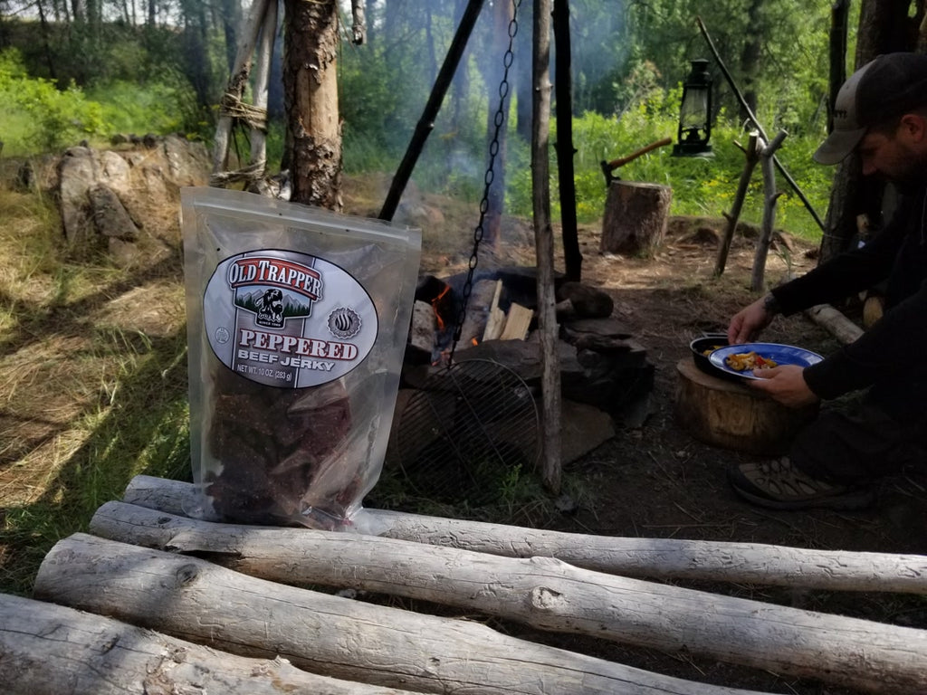 Peppered Beef Jerky next to logs and a campfire.