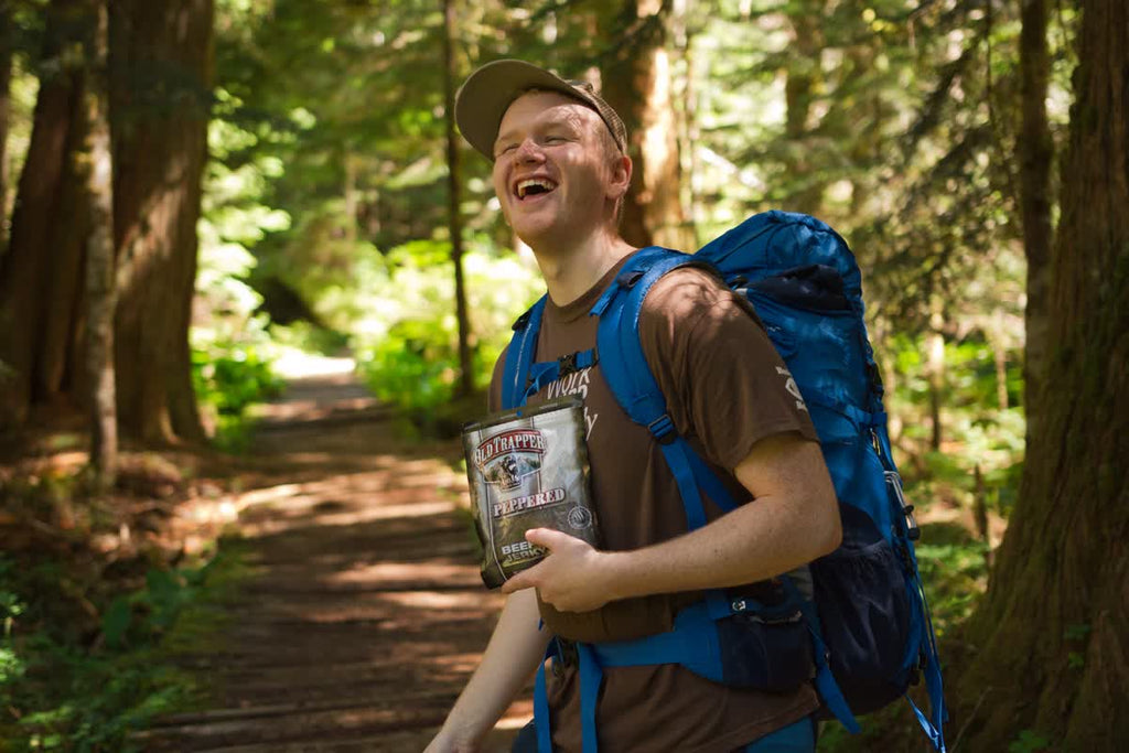 A hiker enjoying a bag of Old Trapper Peppered beef jerky while on the trail.