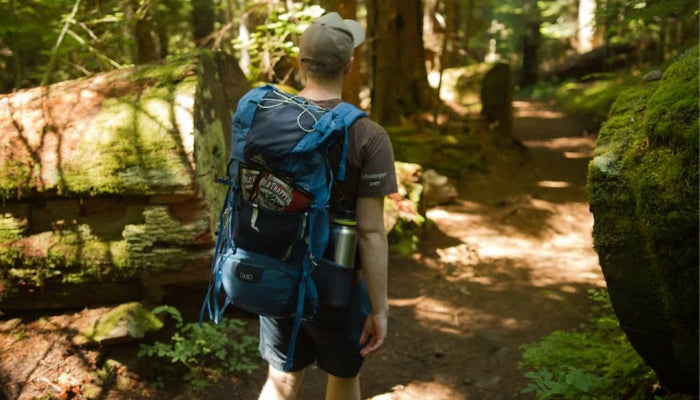 Man hiking with Old Trapper Beef Jerky in his Backpack