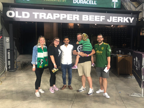 Old Trapper sweepstakes winner posing with Andrés Flores of the Portland Timbers.
