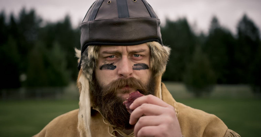 Old Trapper Wearing a Old Fashioned Football Helmet While Snacking on Jerky