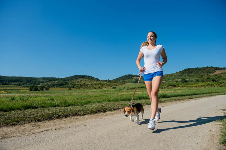 Woman running with Beagle