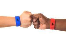 Fist bump wearing pavlok red and blue band.