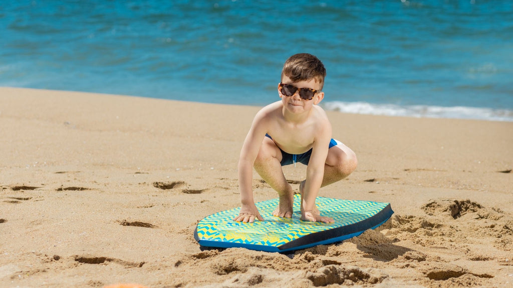 Kid Practicing to Surf in the Shore