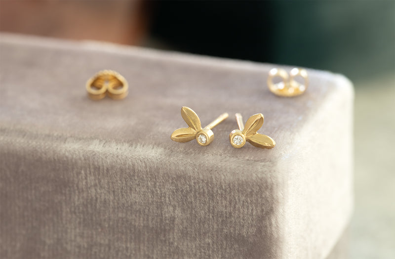 A pair of yellow gold earrings in the shape of two leaves sprouting from a diamond center is pictured on a light gray velvet background.