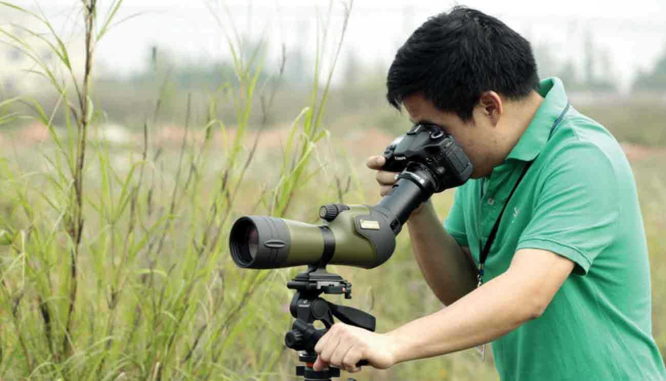 Man using tripod with spotting scope