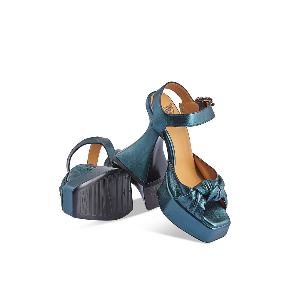 John Fluevog's iconic Munster vaulted to fame when club queen Lady Miss Kier wore a pair on the cover of Deee-Lite's 1990 album World Clique. With the new Mega Munster 'Deee', John returned to Louis IV inspiration and released this stunning platform sandal featuring a knotted leather detail, luscious curves and a deep green leather with a subtle metallic finish. Truly Deee-vine!