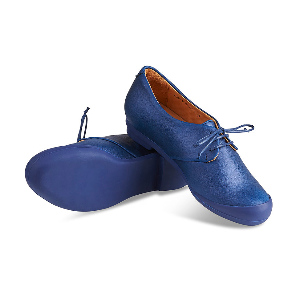 The iconic Geek by Tracey Neuls returns this season with a new rounder toe shape, making it more comfortable than ever. An ideal alternative to a trainer, this wear-anywhere style was described by The London Design Museum as 'a beautiful shoe for an active life'. This new version features a soft and shimmering navy lamé upper and dark navy rubber sole.