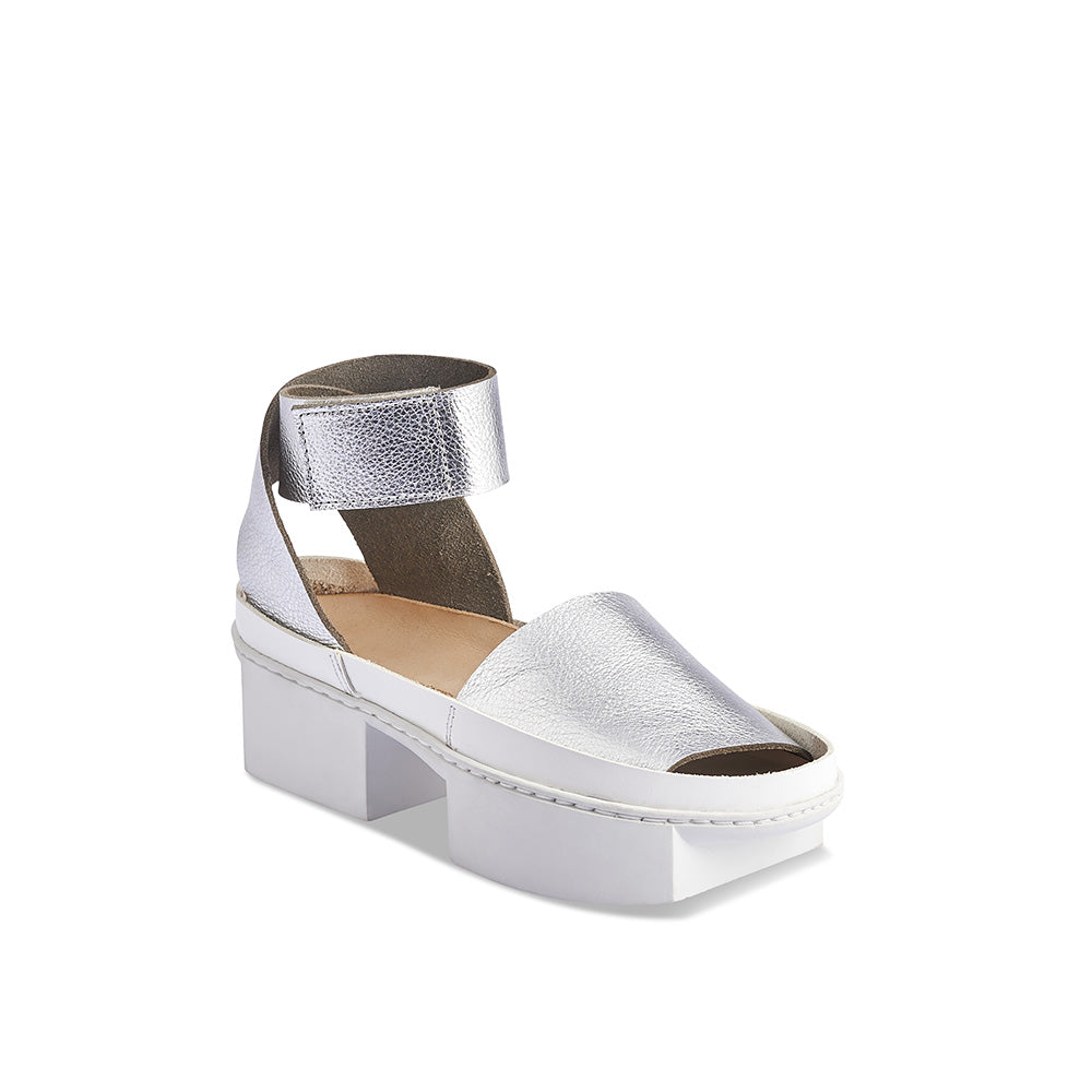 The stunning Reflect features a shiny nickel leather upper and sits atop Trippen's striking 'Box' platform sole. Deceptively comfortable and suitable for all-day wear, the broad unlined leather ankle strap fits securely around the ankle for an easy, adjustable fit.