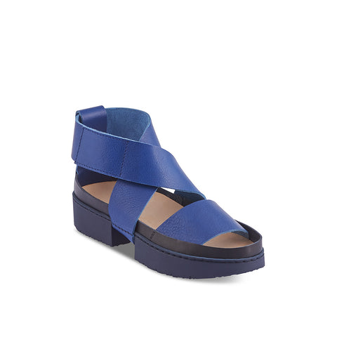 A modern sandal on Trippen's Sport sole, Current features a broad unlined leather cross-strap that secures neatly at the side. This chic sandal combines graphic lines and a contrast leather trim with a wear-anywhere low platform rubber sole.