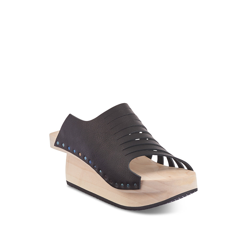 A modern wooden sandal by Trippen, Flux sit atop the new Hover sole that is undercut at one side and has an inward-fanned shaft. The soft unlined leather upper neatly embraces the foot and the contoured footbed provides a supportive fit.