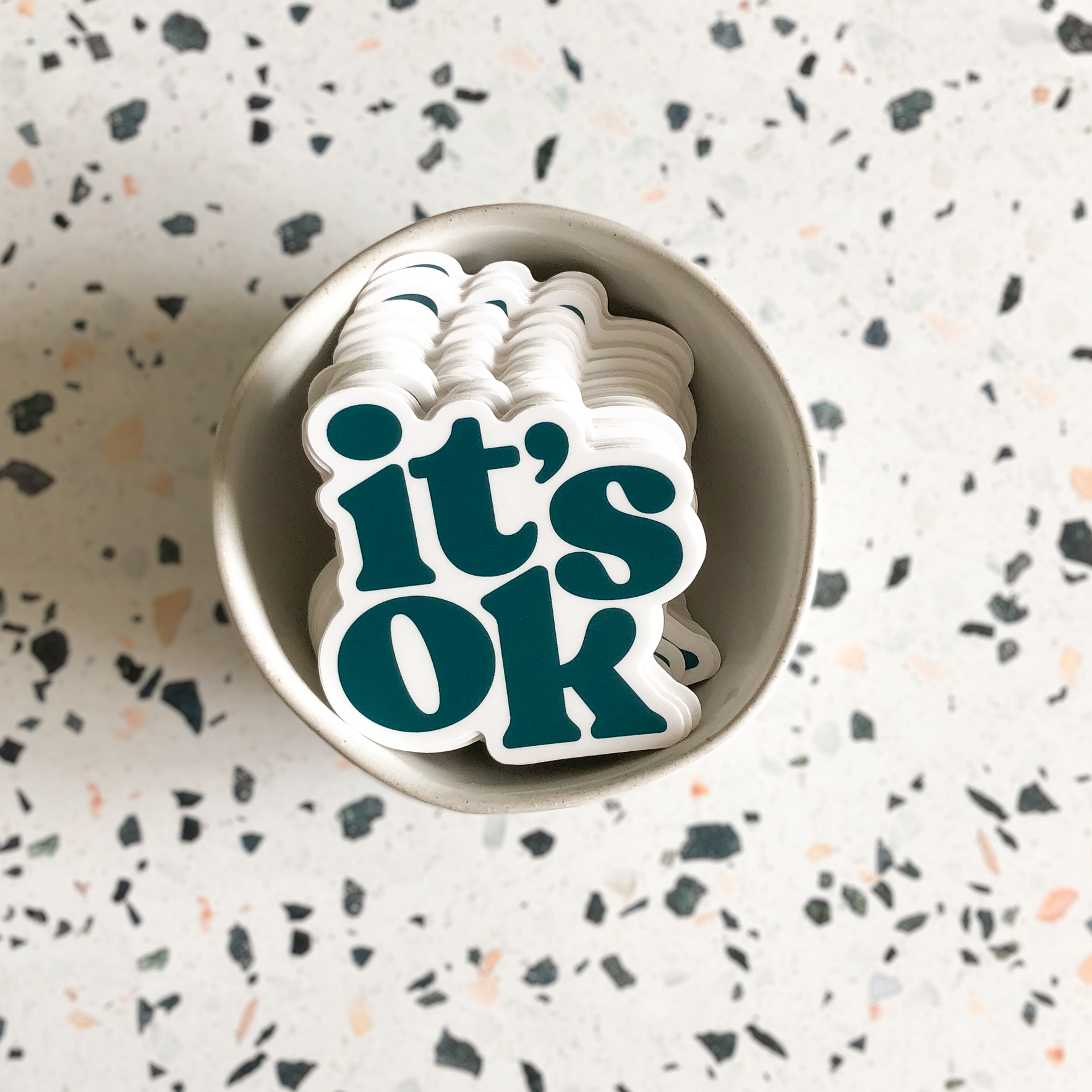 Stack of It's Ok teal stickers in a small bowl.