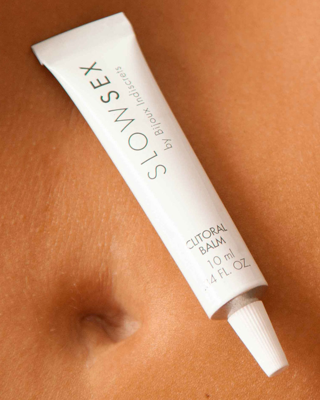 Bijoux Indiscrets Slow Sex Clitoral Balm tube on mode's stomach