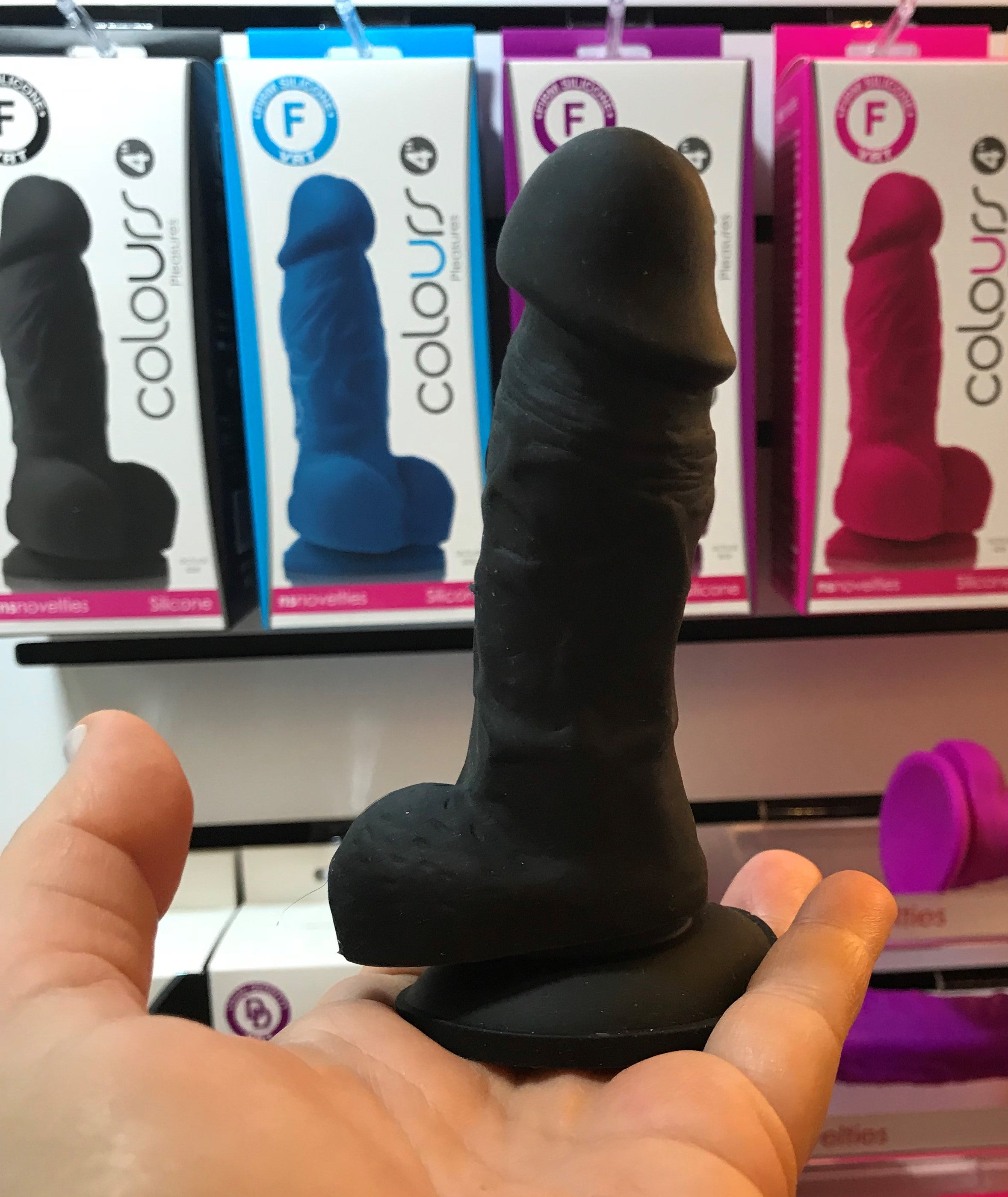 Colours Pleasures Realistic 4 Inch Silicone Dildo by NS Novelties - black  dildo held in the palm of a hand to illustrate the petite size