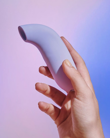 Dame Aer Clitoral Suction Vibrator  held in a hand on a lavender background to show the size