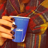 Woman holding a Lavazza Paper cup and enjoying her cheap coffee supplies