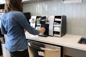 Woman using a Keurig K150 office coffee machine, Keurig UK, Starbucks coffee pods