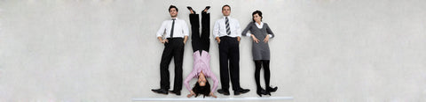 Four office workers, one doing a handstand, who are looking forward to their office coffee