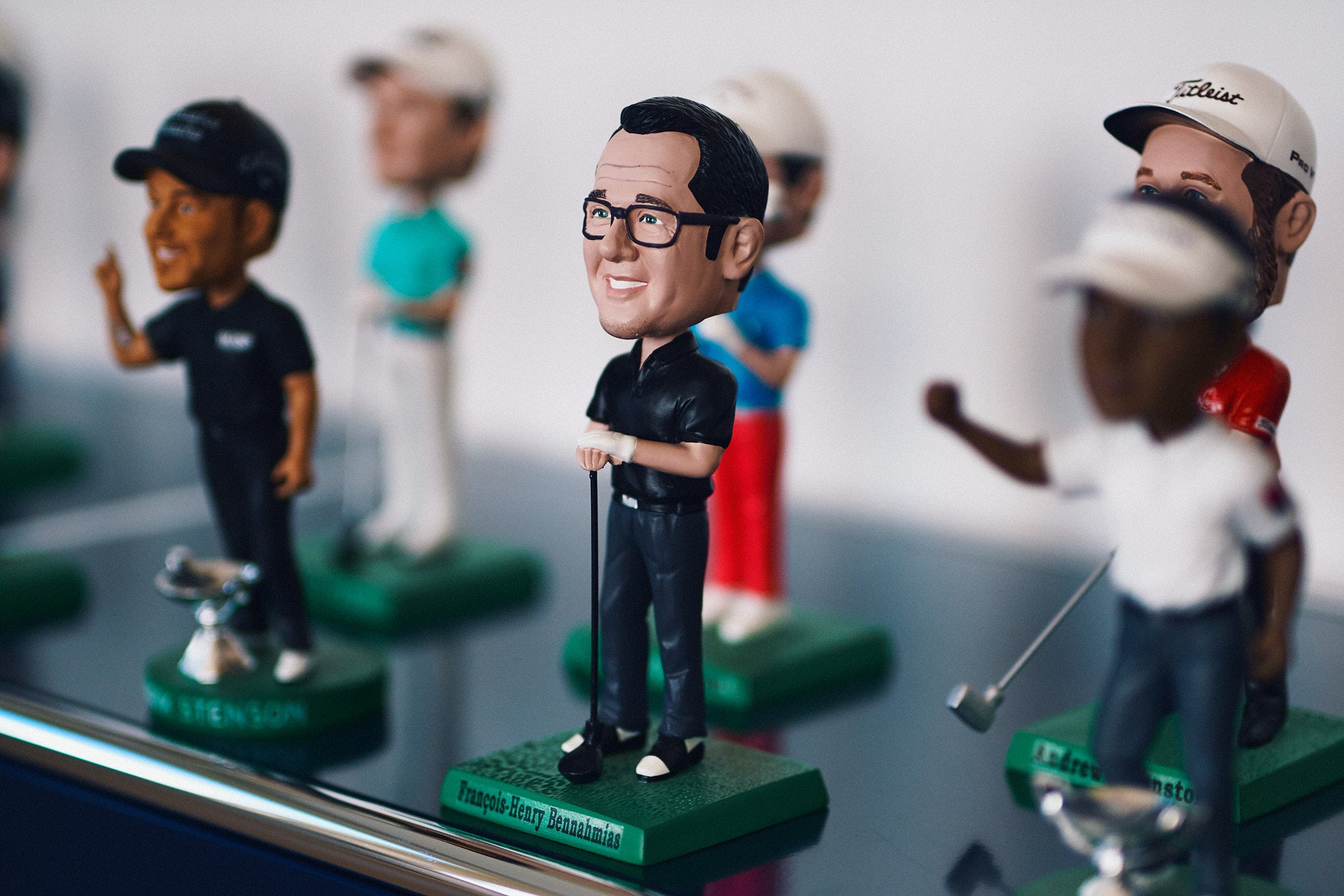 François-Henry Bennahmias CEO of Audemars Piguet AP golfing bobble head with gold professional bobble heads in his office in Le Brassus for A Collected Man London