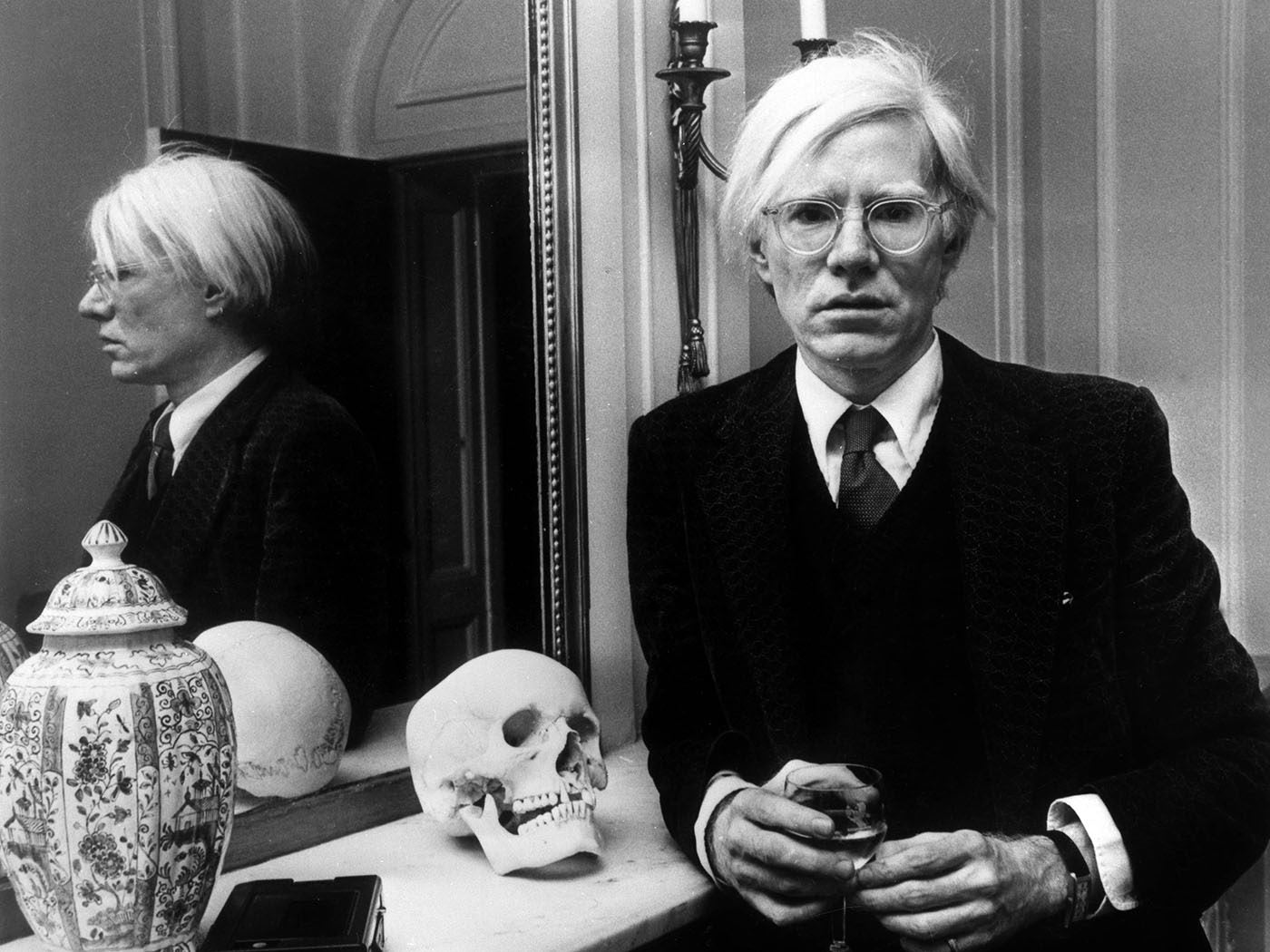 Andy Warhol lent on mantel piece wearing Cartier Tank in Understanding Andy Warhol as a collector for A Collected Man