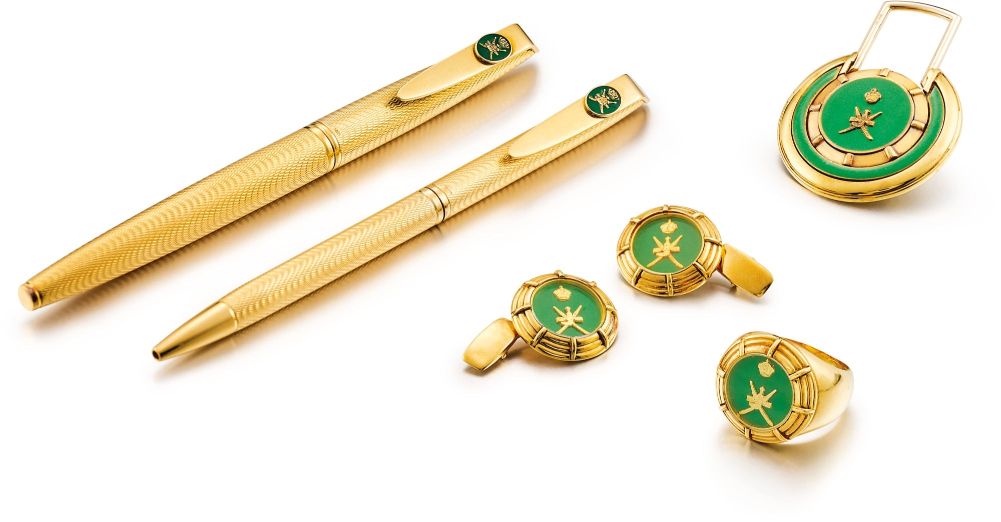 A set of gold pens, cufflinks, a ring and money clip all bearing the Omani Khanjar for A Collected Man London