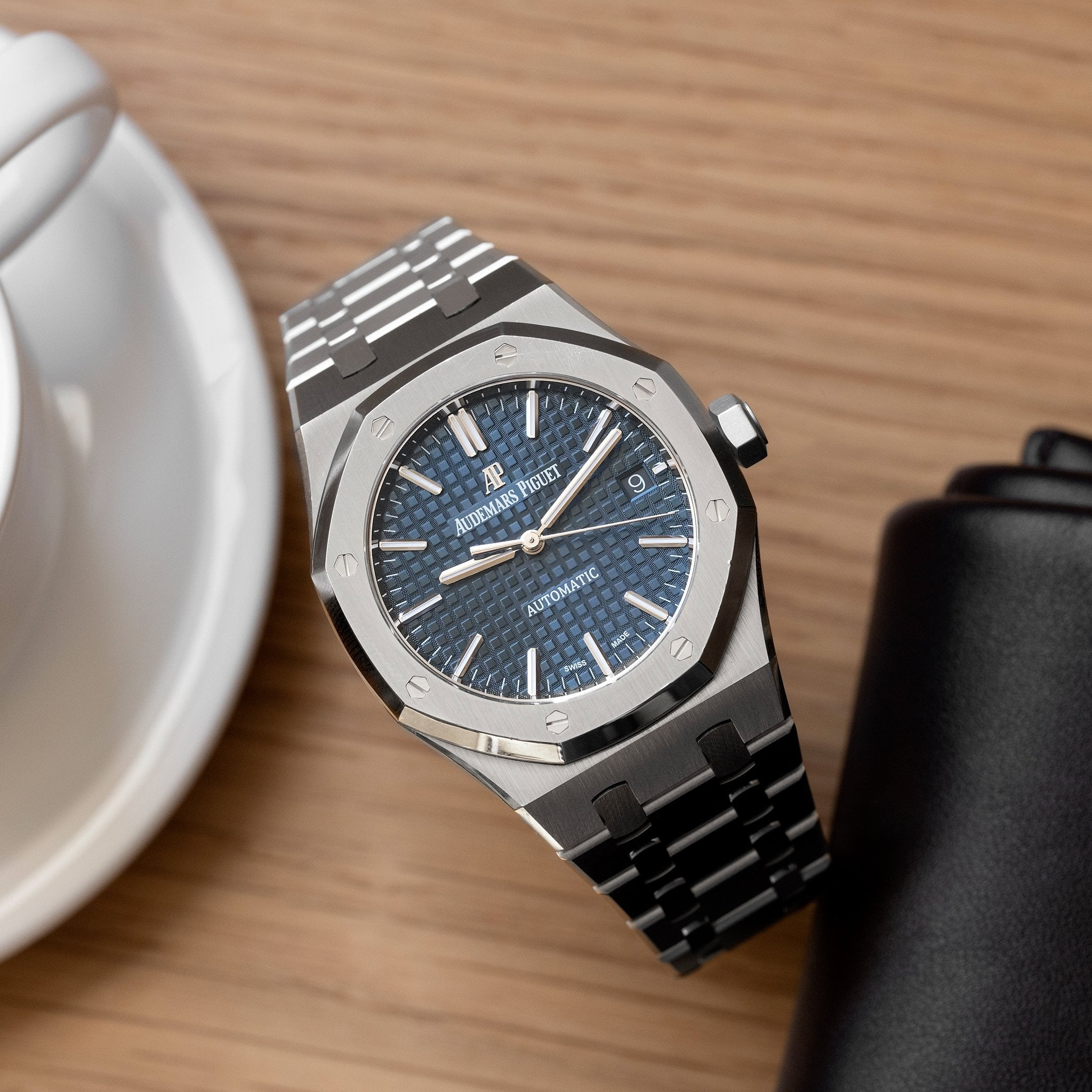 Audemars Piguet Royal Oak on wooden table in Five Collectors Choose their Favourite Date Disc for A Collected Man London