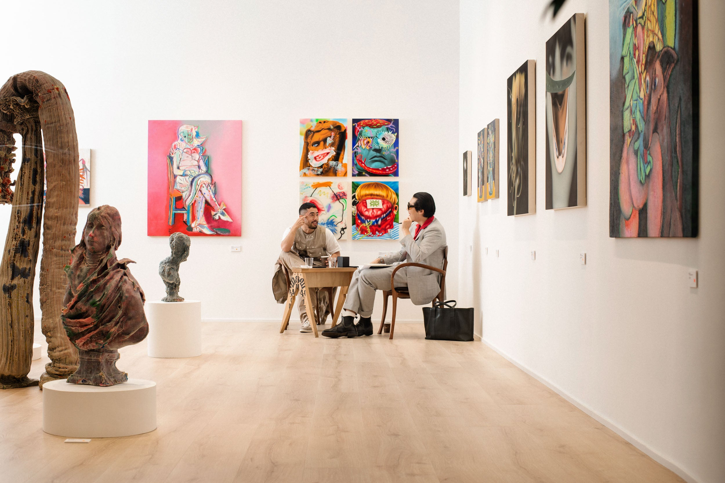 Kevin and Randy sat at table in distance in Obsessions: Contemporary Culture with Kevin Poon for A Collected Man London