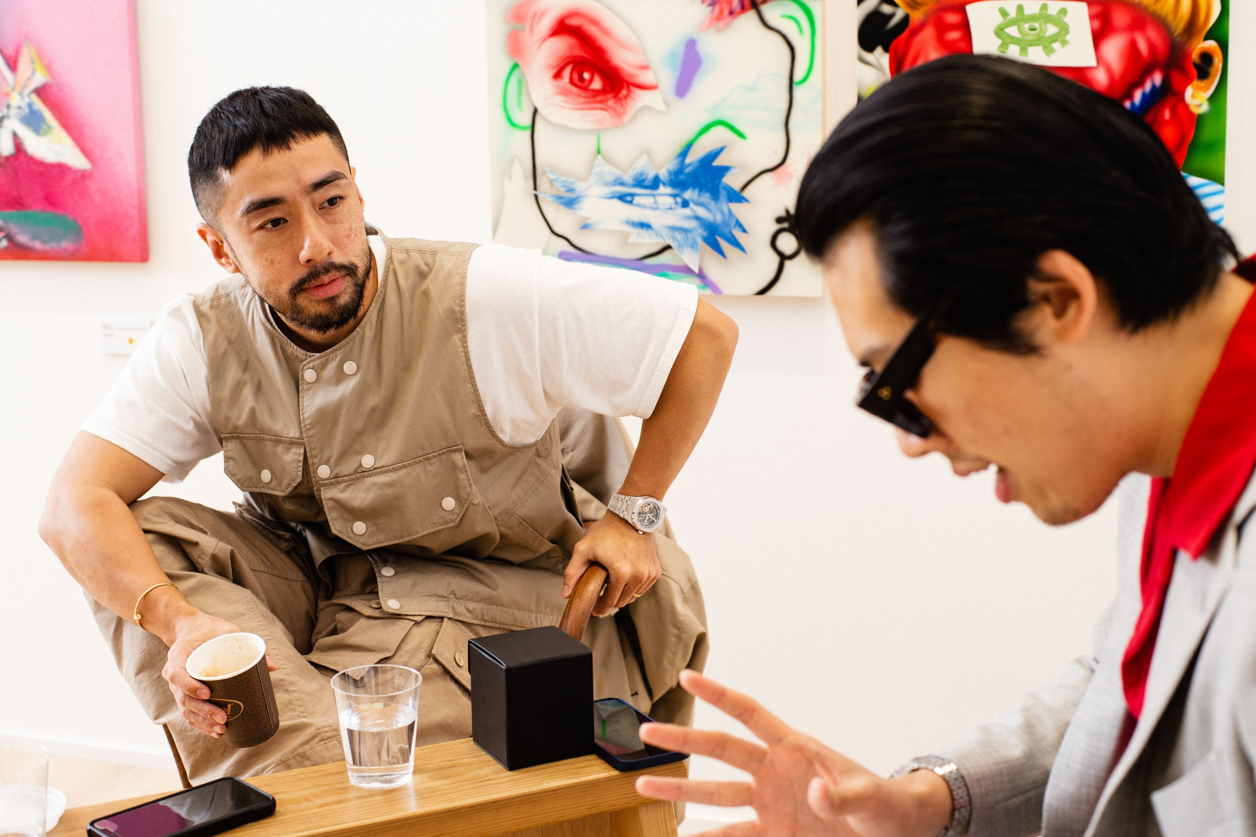 Poon and Randy talking at table in Obsessions: Contemporary Culture with Kevin Poon for A Collected Man London