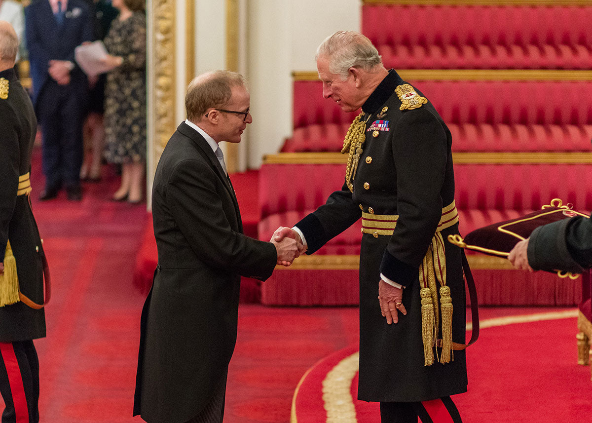 Roger W. Smith watchmaker receiving his OBE from Prince Charles for A Collected Man London