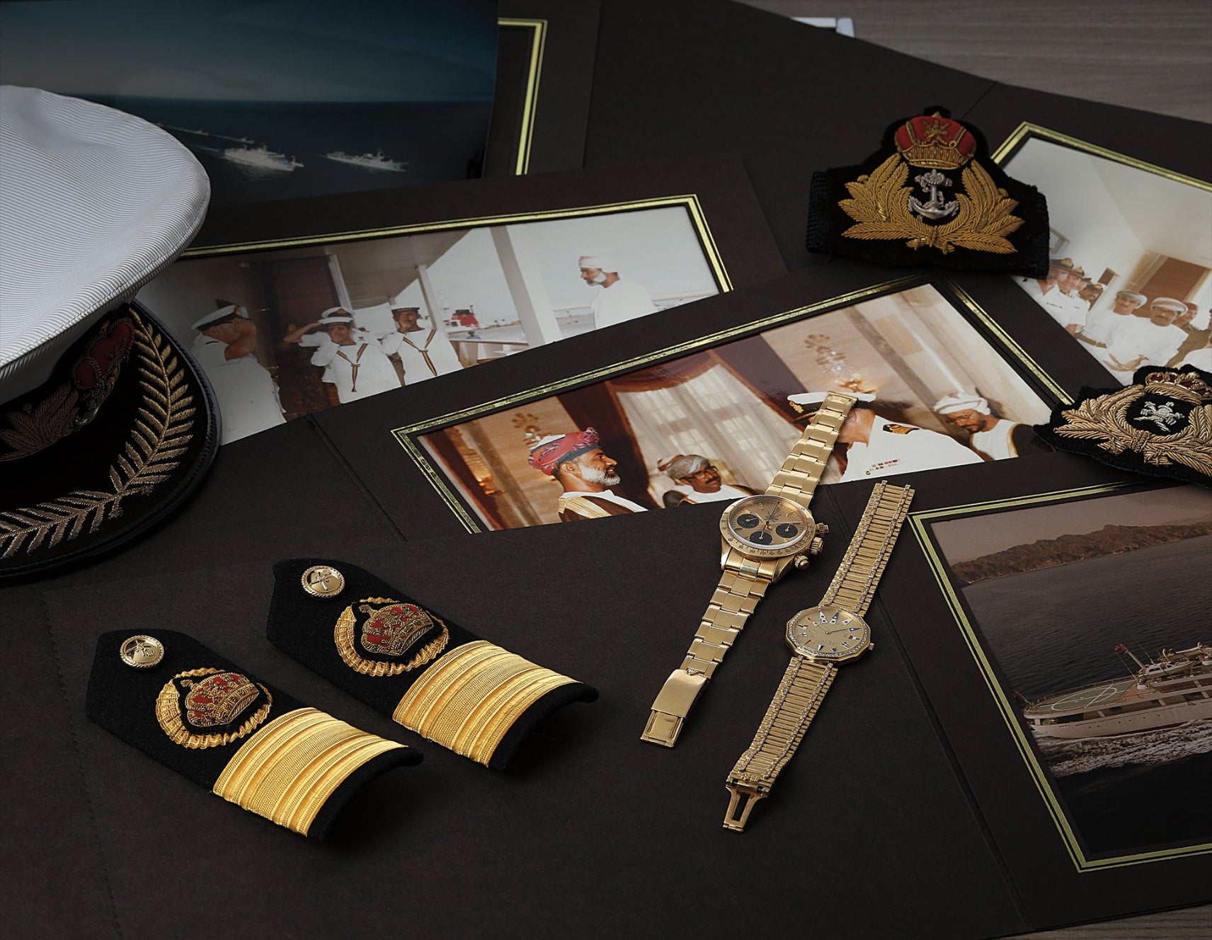 Flat lay of a Rolex Daytona Khanjar-signed and a gold and diamond watch with pictures of the Sultan of Oman and Military regalia for A Collected Man London
