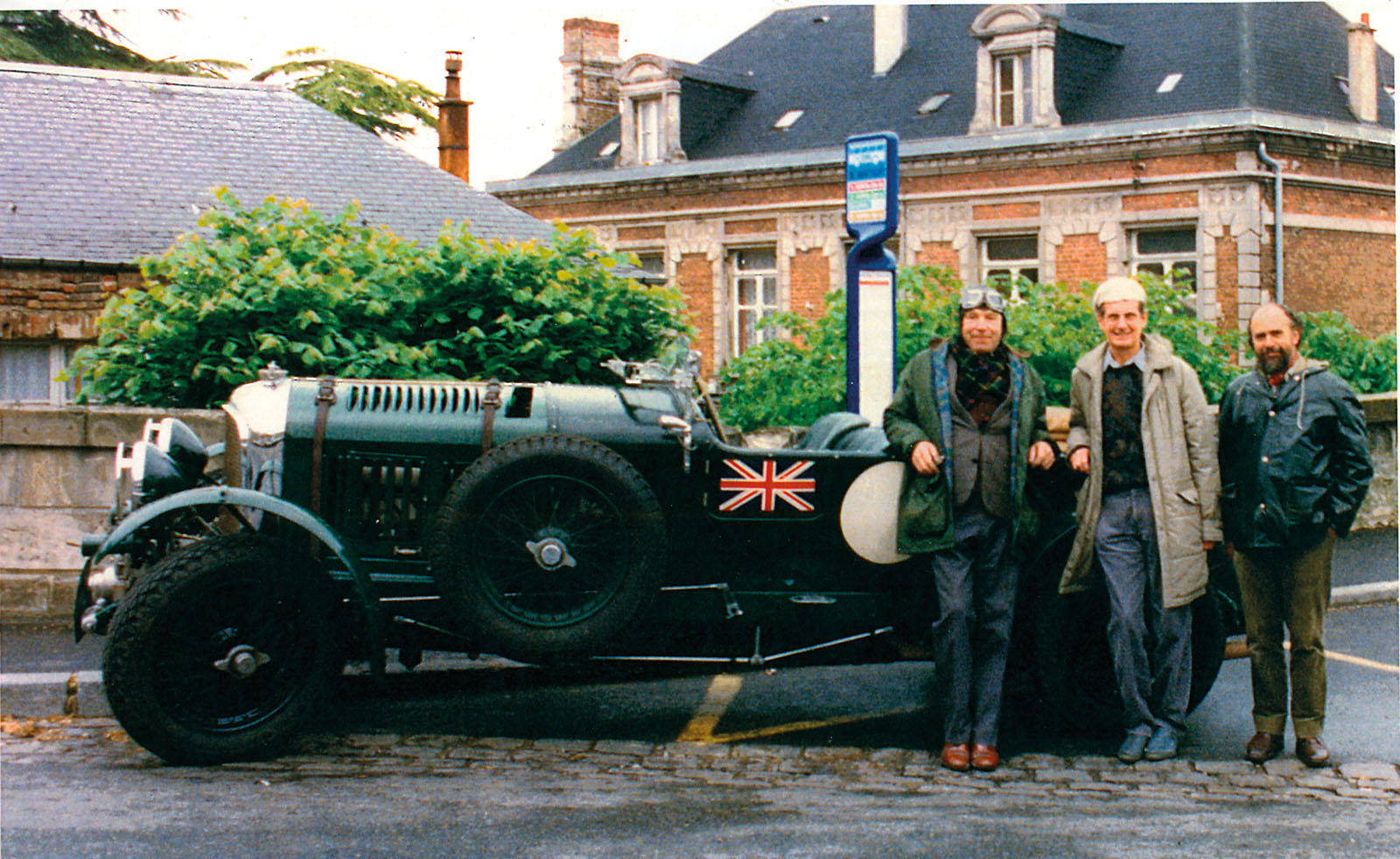 Daniels, Pratt and Grahame Brooks in front of a car in Three Watchmakers' Unfinished Watches for A Collected Man London