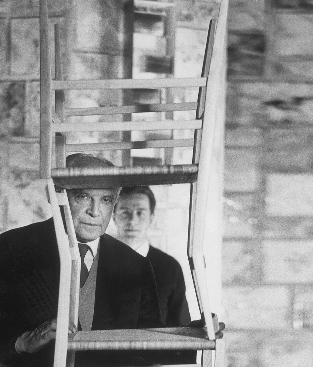 Gio Ponti and son looking through a stack of Superleggera chairs in The Eclectic Life and Work of Gio Ponti for A Collected Man London