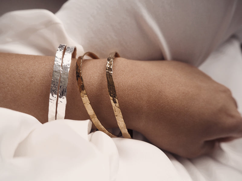 The Yan Neo Enyo Silver Hammered Metal Enyo Bracelets worn with gold