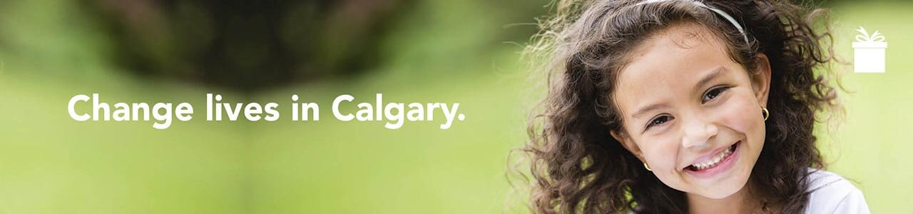 Change lives in Calgary. A young girl with curly hair smiles.