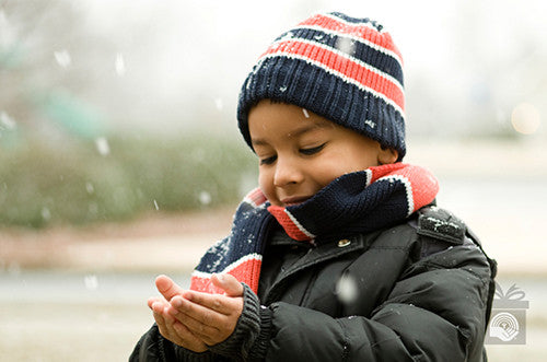 A young boy bundled up in a puffy coat, scarf and hat catches snow flakes in his hands