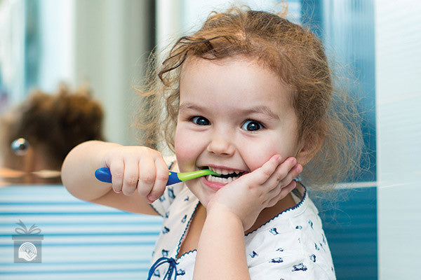 A young girl smiles while brushing her teeth in her pyjamas