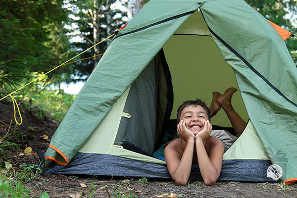A young boy smiles while sitting in a tent