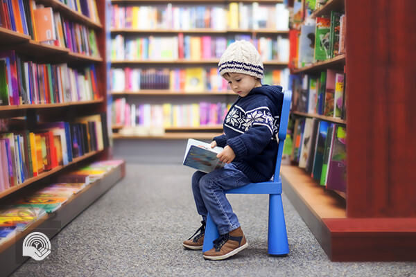 A young boy sits on a stool, reading a book from a shelf in front of him