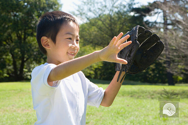 A boy holds his baseball glove out, ready to catch a ball