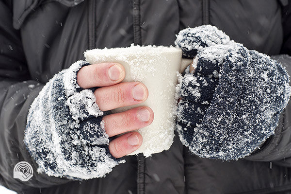 Someone warms their snow covered mittens and hands on a mug