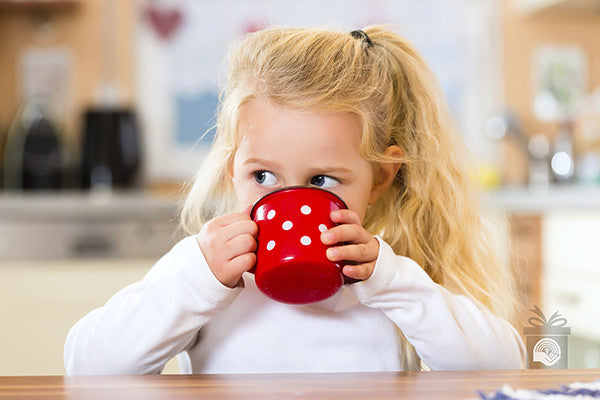 A young girl drinks milk from a red cup